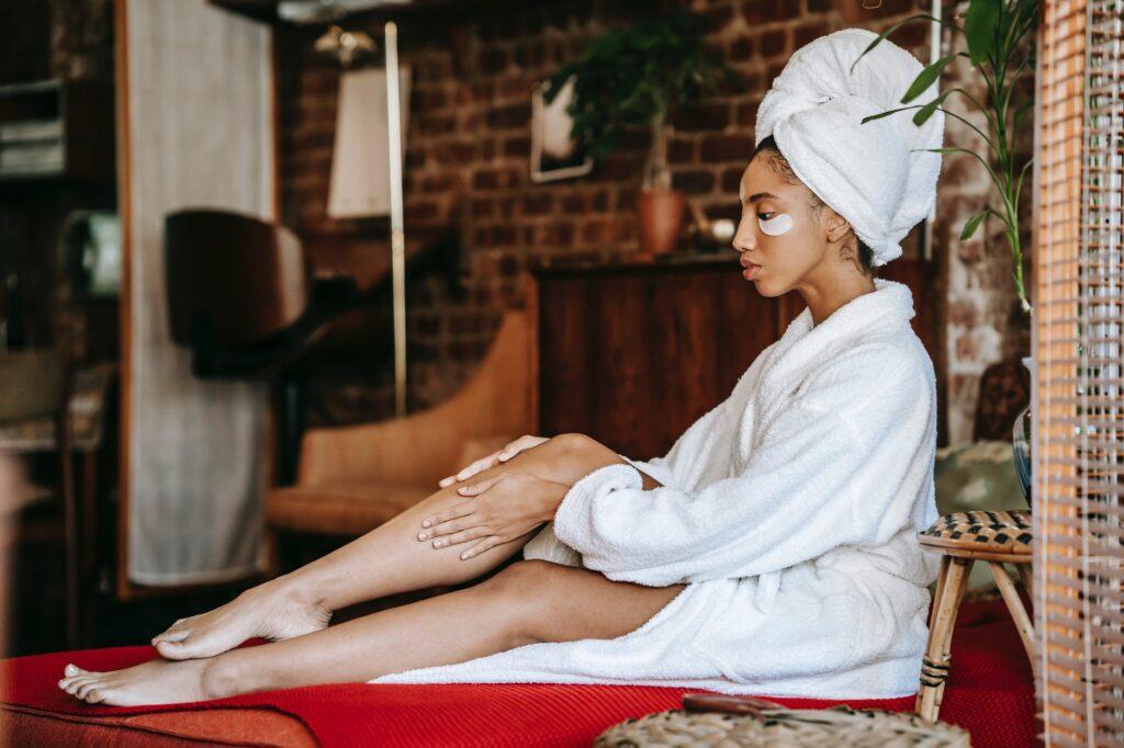 woman in bathrobe applying cream on leg